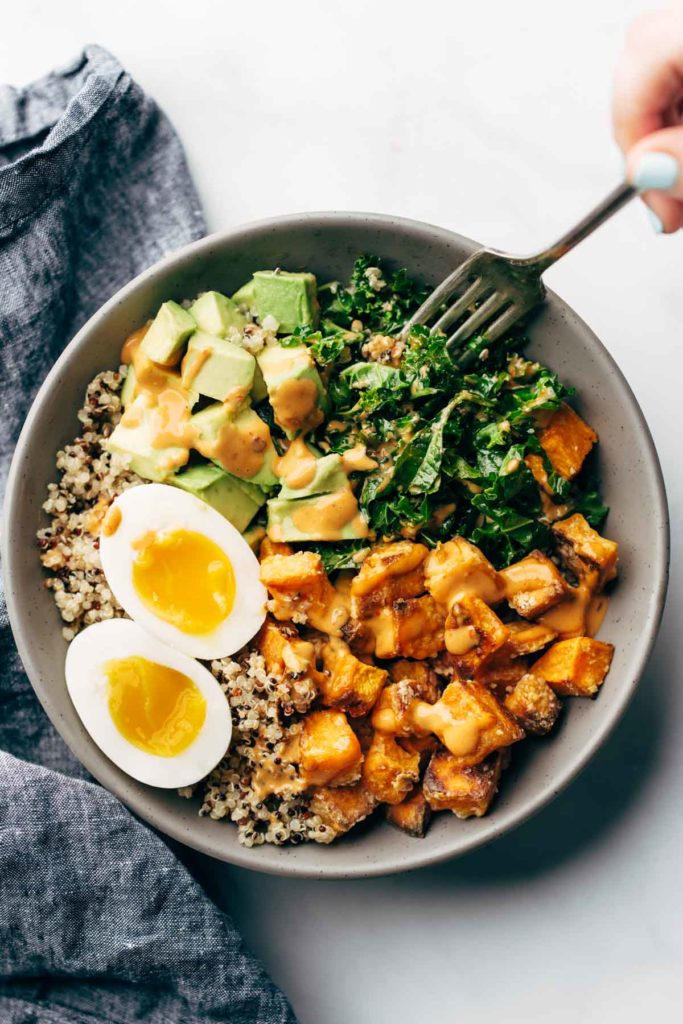 A loaded bowl with rice, eggs, greens, and other ingredients photographed from overhead